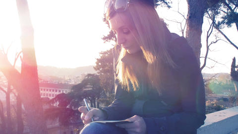 young woman writing her thoughts in a diary at the sunset in park Footage