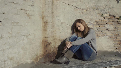 sad young woman sitting on the ground: depression, desperate woman, loneliness Footage