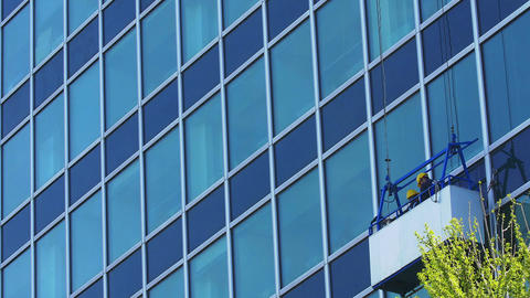 Workers clean and seal glass windows of highrise building Footage