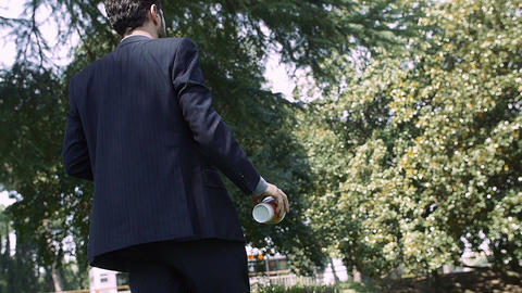 rude businessman drinking coffee in the park: throws away the cup onto the grass Footage