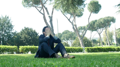 discomforted businessman sitting on the grass in a public park: sad businessman Footage