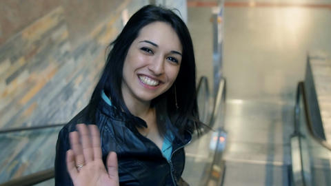 young woman greets with her hand on escalator at the train station Footage