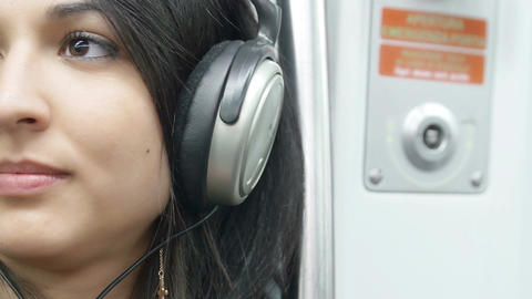 cute young woman listening music in the subway train: relaxing with music Live Action