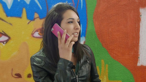 young woman talking at the mobile phone near murals Footage