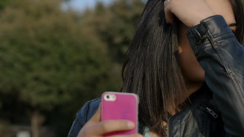 beautiful brunette woman in the sun looking for something on her smartphone Footage