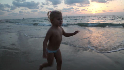 Little girl running along the seashore at sunset Footage