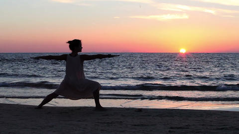Girl performs gymnastic exercise on the beach in the evening Footage