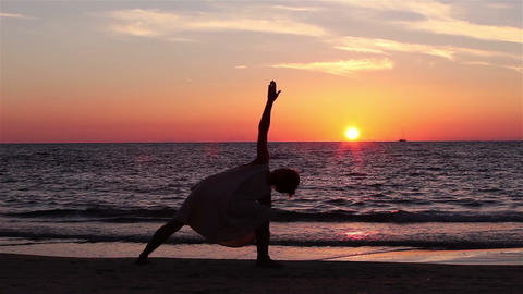 Silhouette of a woman who performs yoga exercises at sunset by the sea Footage
