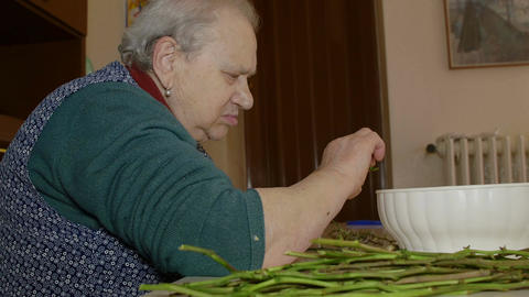 very old woman cooking wild asparagus Footage
