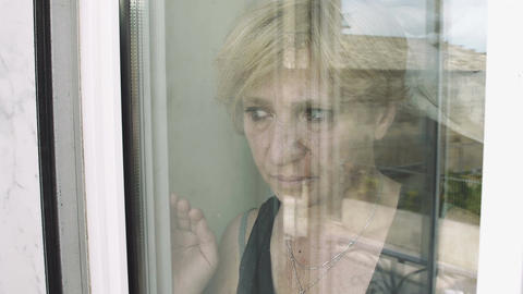 sad mature woman looking out her house from beyond the window Footage