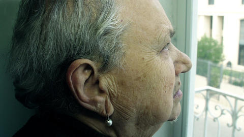 depressed and lonely elderly woman waits for someone and looks out the window Live Action