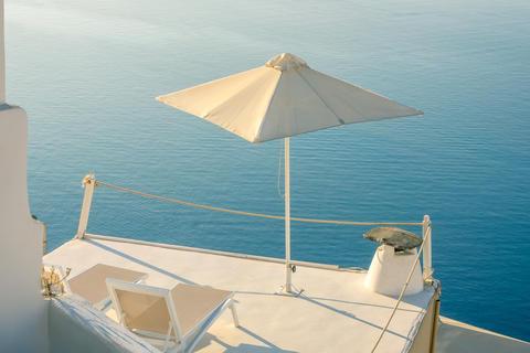 Two Sun Loungers and an Umbrella on the Balcony of Santorini Fotografía
