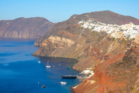 White Houses in Oia on a Sunny Day and Several Yachts Parked Nea Fotografía