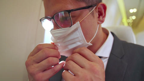 Traveler wearing face mask while traveling on commercial airplane Live Action