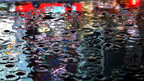 3D animation of the rain droplets in a street puddle with a reflections of night city traffic Animation