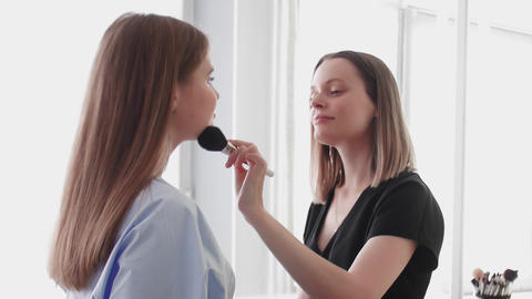 Make-Up Artist Beautician Applying Cosmetics On Young Caucasian Woman Live Action
