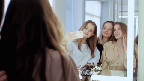 Confident caucasian adult makeup artist with two young model in beauty studio Live Action