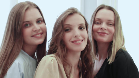 Happy caucasian adult makeup artist with two young model in beauty studio Live Action