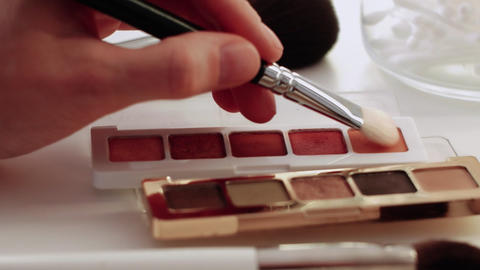 A palette with eye shadows and a makeup brush. Close up of woman make up Live Action