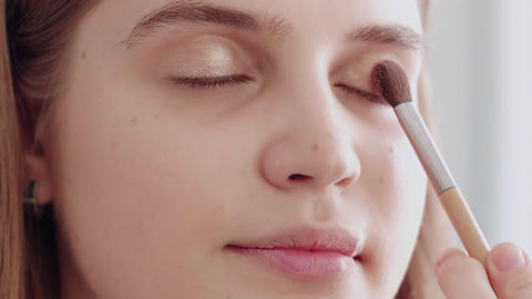 Make-up artist puts color eye shadow on a beautiful model. Make-up artist work Live Action