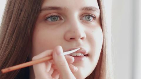Professional make up artist applying liquid lipstick on lips Live Action