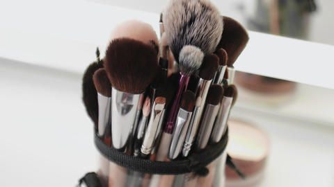 Close up of Many different makeup brushes on the table Live Action