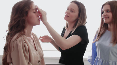 Professional make up artist teacher training her young student to become makeup Live Action