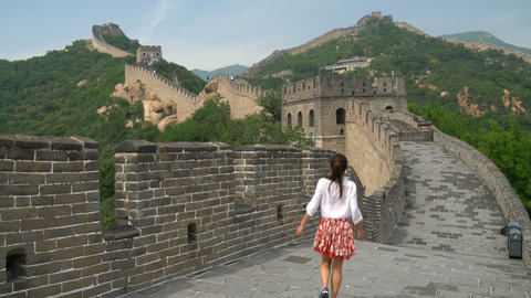 Fun happy cheerful joyful tourist woman at Great Wall of China having fun travel Live Action
