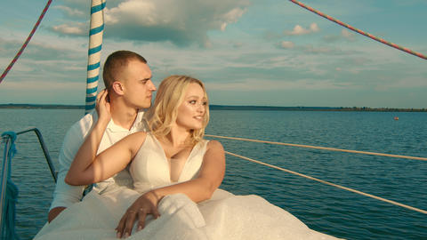 The bride and groom are sitting on a yacht. Looking into the distance at sunset Live Action