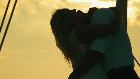 Black silhouette of two lovers. Newlyweds at sunset. The groom kisses the bride Live Action