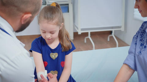 Doctor bandaging child hand Live Action