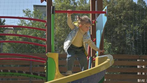 Little blond girl preparing to slide at children's slide at playground Live Action