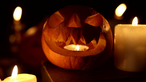 Smiling Halloween pumpkin in candlelight shines at night as a looped lantern Live Action