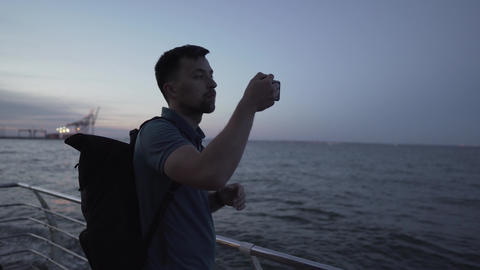 Man photographs landscape of the sunset at sea. Male traveler blogger. Traveler Live Action