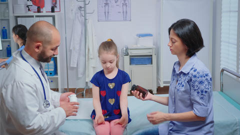 Pediatrician giving mother a bottle of pills Live Action