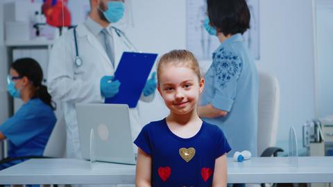 Portrait of little girl smiling in medical office Live Action