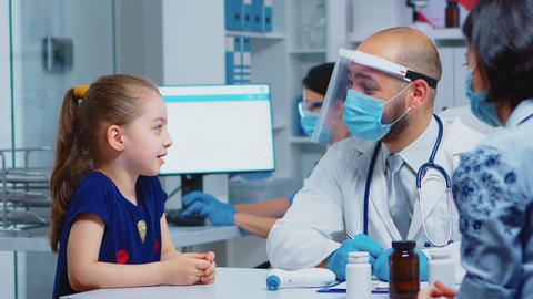 Doctor talking with child wearing protection mask Live Action