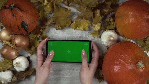 Woman is holding smartphone with green screen and makes playing gestures Live Action