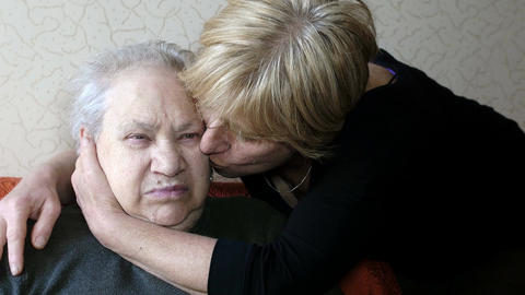 mature daughter comforting her old mother at home: elderly pensive woman Footage