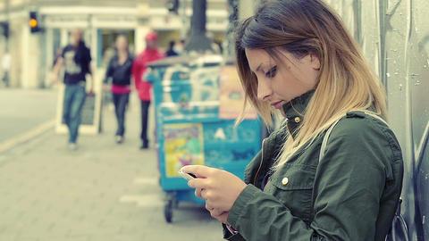 young lonely woman writing text message on the mobile phone in the city ビデオ