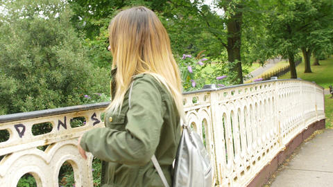 young girl walking towards the camera and leans on the railing of a bridge Footage