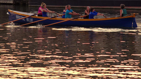 rowing boat at the sunset with people in athletic training Live Action