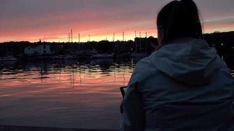 young woman making photos with a tablet computer sitting on the dock of a harbor Footage