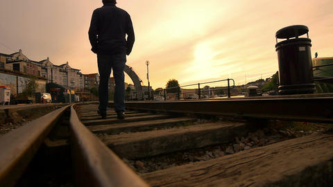 lonely man walking in the middle of an old railway Footage