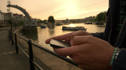 sending messages with the smartphone with river at the sunset in background Footage