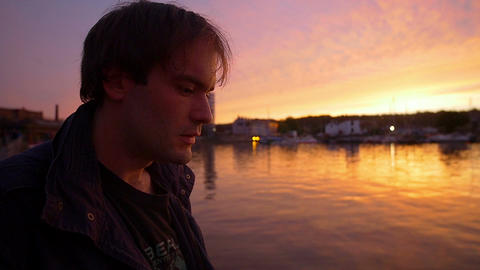 pensive man smoking at the sunset in front of the harbor Footage