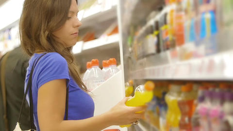 young woman searching soft drinks in the supermarket Footage
