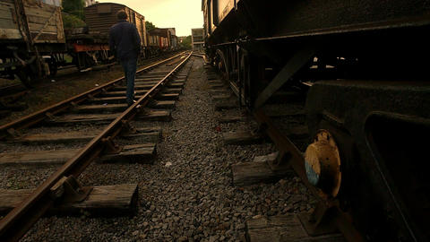 young man walking on the rail tracks in an abandoned station Footage