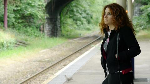sad thoughtful woman waiting the train near the rail tracks Footage