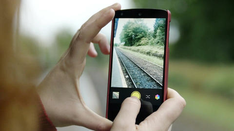 hands of woman using smartphone to make pictures of railtracks, railway Footage